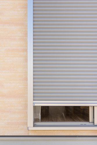 Volet roulant gris intallé à l'extérieur d'une fenêtre pour améliorer la sécurité au sein de votre habitation